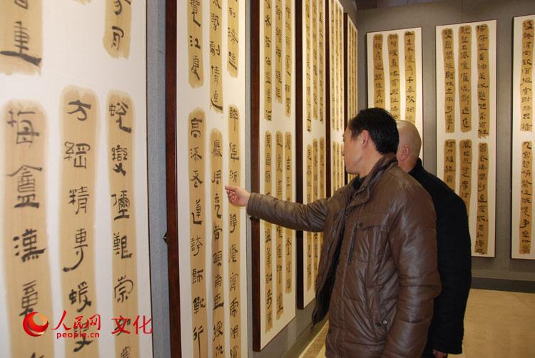 观众正在观赏、品论张继的隶书《中国书画千字文》。(人民网 王鹤瑾 摄)